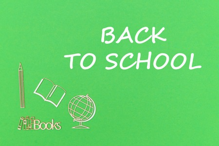concept school for kids, text back to school, school supplies wooden miniatures on green backboard