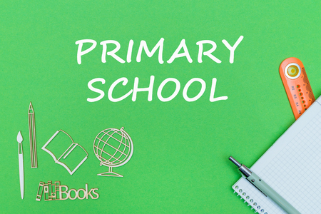 concept school, text primary school, school supplies, notebook, ruler and pen on green backboard Stock Photo