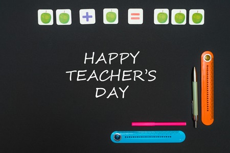 Concept school, black art table with stationery supplies with text happy teachers day on blackboard Stock Photo