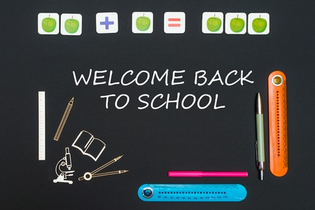 concept back to school, above stationery supplies and text welcome back to school on black backboard Stock Photo