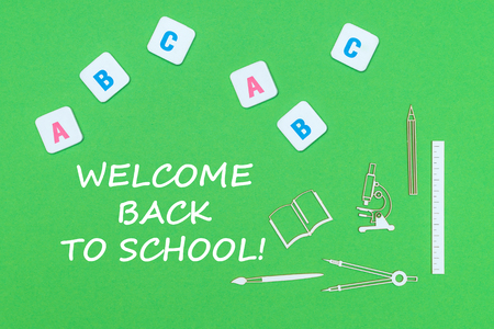 concept school, text welcome back to school, school supplies wooden minitures, abc letters on green backboard Stock Photo