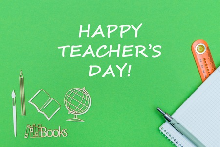 concept school, text happy teachers day, school supplies, notebook, ruler and pen on green backboard