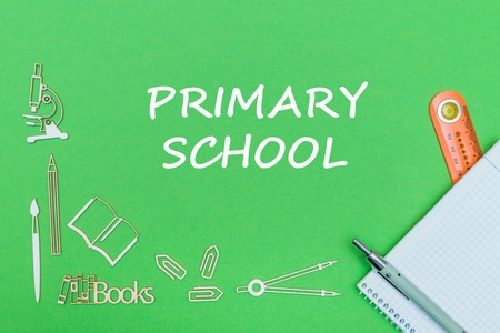 concept school, text primary school, school supplies wooden miniatures, notebook with ruler and pen on green backbord
