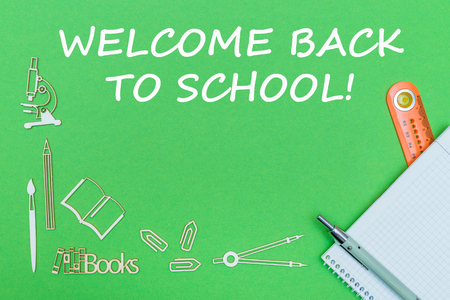 Concept school, text welcome back to school, school supplies wooden miniatures, notebook with ruler and pen on green background Stock Photo