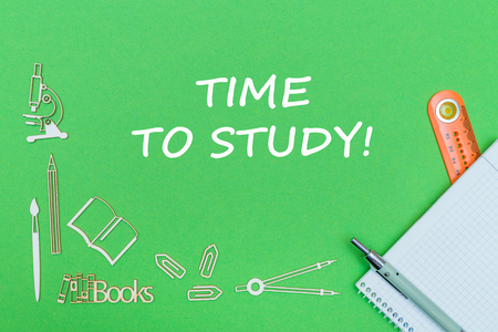 concept school, text time to study, school supplies wooden miniatures, notebook with ruler and pen on green backbord Stock Photo