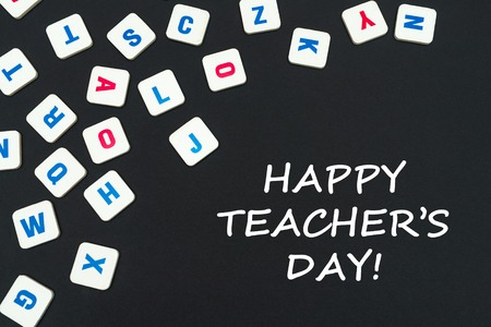 english school concept, text happy teachers day, colored square english letters scattered on blackboard