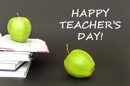 Concept back to school, text happy teachers day, two green apples, open books on gray background Stock Photo