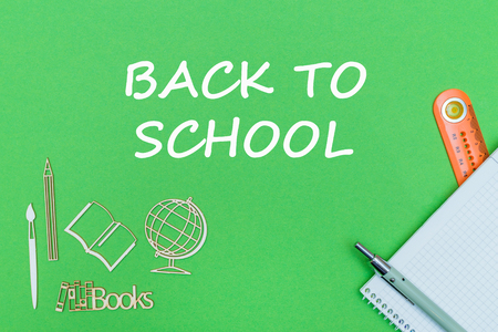 concept school, text back to school, school supplies, notebook, ruler and pen on green backboard Stock Photo