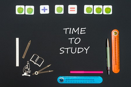 Concept back to school, above stationery supplies and text time to study on black background Stock Photo