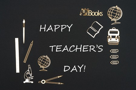 Concept back to school, text happy teachers day with school supplies chipboard miniatures placed on blackboard Stock Photo