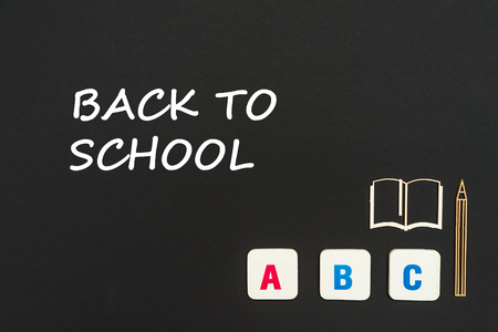 Concept english school, text back to school, abc letters, chipboard miniature book, pen on blackboard