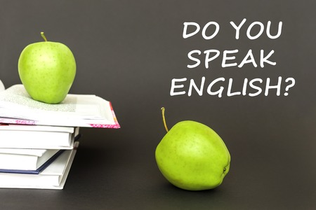 Concept back to school, text do you speak english, two green apples, open books on gray background Stock Photo
