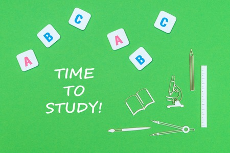 Concept school, text time to study, school supplies wooden minitures, abc letters on green background Stock Photo