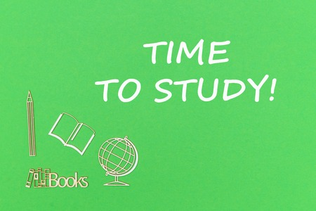 Concept school for kids, text time to study, school supplies wooden miniatures on green background Stock Photo