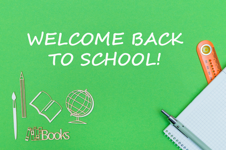 Concept school, text welcome back to school, school supplies, notebook, ruler and pen on green background