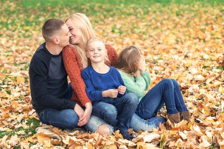 Happy family couple with children kissing in autumn park. Family concept