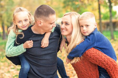Mother and father carrying their two adorable children on shoulders look at each other during warm autumn weekend. Smiling family in autumn park. Stock Photo