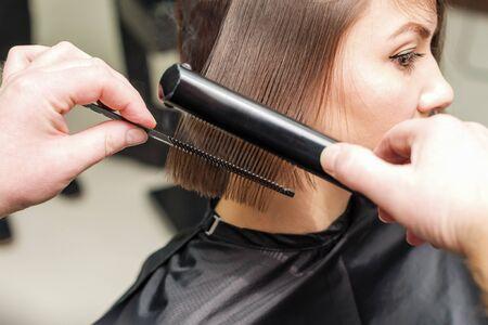 Professional hairdresser begins to do hairdo for girl Stockfoto