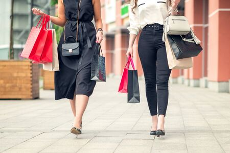 Low angle shot of two girls walking near shopping center together carrying colorful paperbags after day of purchases.