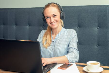 Smiling young woman wearing headphones and is sitting in front of an open laptop at a table at cafe. Business concept