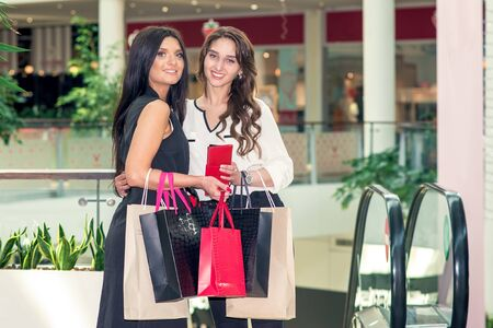 Two girls looking at the camera and holding packages at the mall. Girls are shopping on a black Friday. Shopaholics and stores concept.
