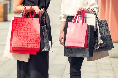 Two young girls after shopping with bags in hands near shopping center. Shopaholics and stores concept.