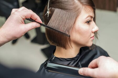 Professional hairdresser combing with a comb short hair. Hair salon. Woman haircut. Cutting Stockfoto