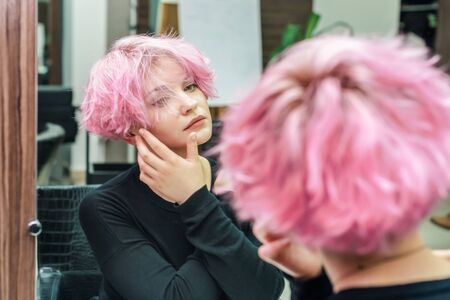 Beautiful hairstyle of young woman looking in the mirror after dying hair and making highlights in beauty salon. Close up short pink hairdo