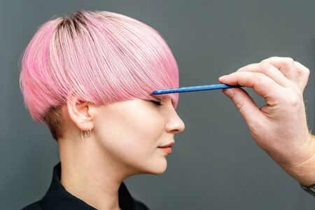 Professional hairdresser combing with a comb short pink hair. Hair salon. Woman hairdo. Close up. Copy space