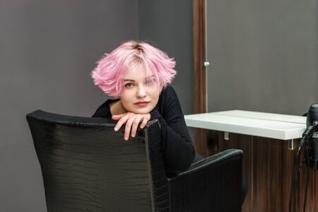Beautiful hairstyle of young woman after dying hair and making highlights in beauty salon. Close up short pink hairdo