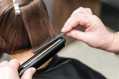 Professional hairdresser straightening short brown hair with hair straighteners in beauty salon, concept barber salon, female stylist.