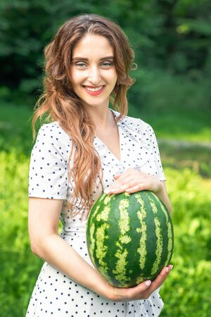 smiling woman is holding watermelon in white dress on green nature background, young brunette with watermelon Stock Photo