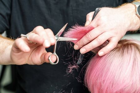 professional hairdresser is holding in hand between fingers lock of red hair and cuts hair tips, beauty hairstyle concept