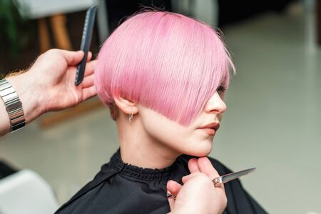 the hairdresser completed making a pink short haircut with comb and scissors, master class for coloring hair