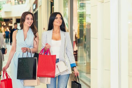 two smiling young women are walking with bags in shopping mall, shopping concept Stock fotó