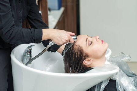 professional barber is washing the girls hair in the barbershop, concept barber salon, female stylist Zdjęcie Seryjne