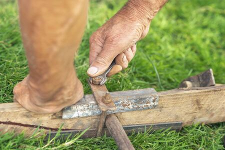 hands of an elderly man twist the nut with a wrench on green grass