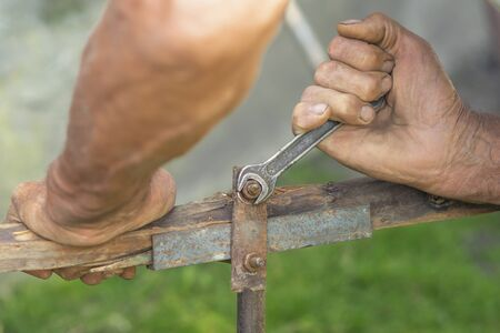 a hand of an elderly man is twisting the nut with a wrench outdoors, repair with hands