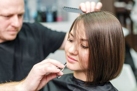 Stylist is cutting woman hair and making new hairdress in salon. Hairdresser cutting clients hair in beauty salon. Hairstyle and people concept