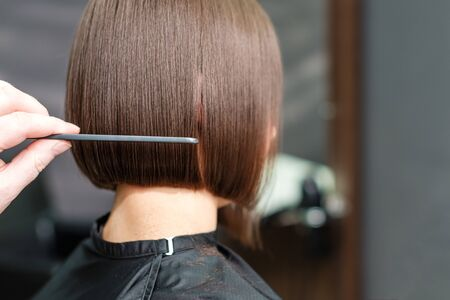 Close up of a hairdresser combs the short brown hair of her client in beauty salon background. Professional hair care concept.