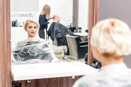 Pretty young woman is looking at the reflection in the mirror while sitting in hair salon and waiting for hairdresser at beauty salon. Zdjęcie Seryjne