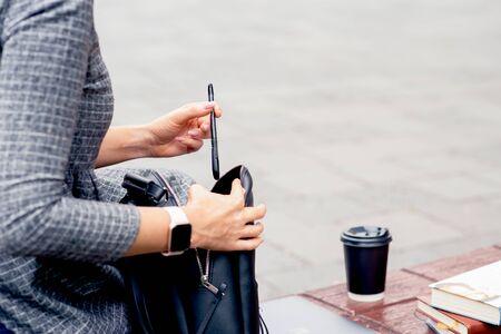 Une étudiante met un stylo à bille dans un sac à dos noir sur un banc. Les mains d'une étudiante mettent un stylo dans un sac à dos à l'extérieur. Concept de vie étudiante.