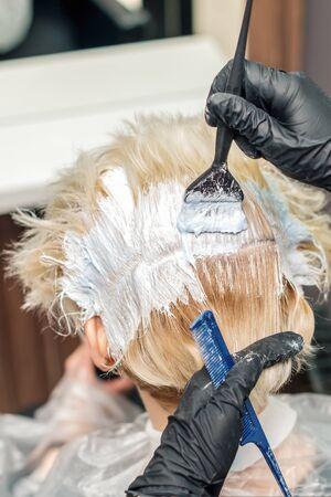 Les mains du coiffeur dans des gants noirs peignent les cheveux féminins dans une couleur blanche en gros plan. Mains de coiffeur avec brosse et peigne se bouchent.