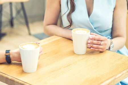 Two female are holding a cups of coffee at cafe close up. Two young woman with cup of coffee at cafe outdoors.