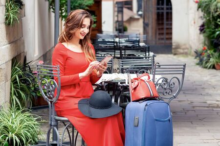 Tourist business woman is wearing red dress with suitcase is using smartphone at sidewalk cafe on the street. Reklamní fotografie