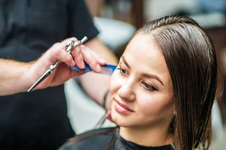 Hairdresser is making hairstyle for young woman with wet brown long hair at hair salon close up.