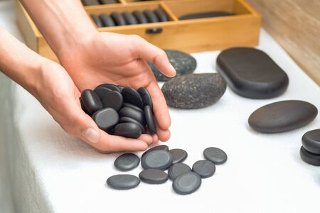 Close up of smooth polished hot massage black stones in mans hands on table in relaxing spa salon