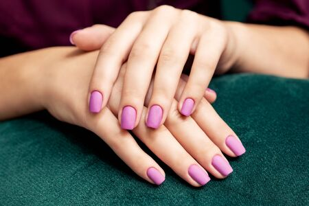 Beautiful purple matte manicure on the womans nails on a dark green fabric background close up.