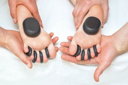 Hot massage stones between the womans toes on the feet while massage therapists holding her feet.