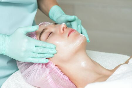 Cosmetologists hands in gloves applying a white cream to the woman face in the spa beauty salon close up. Stock Photo